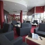 salon de reception avec fauteuils gris au comfort hotel clermont saint jacques