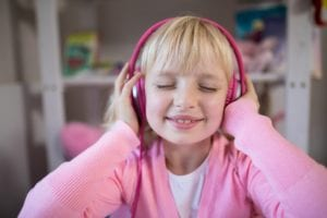 Cute girl listening to pink headphones