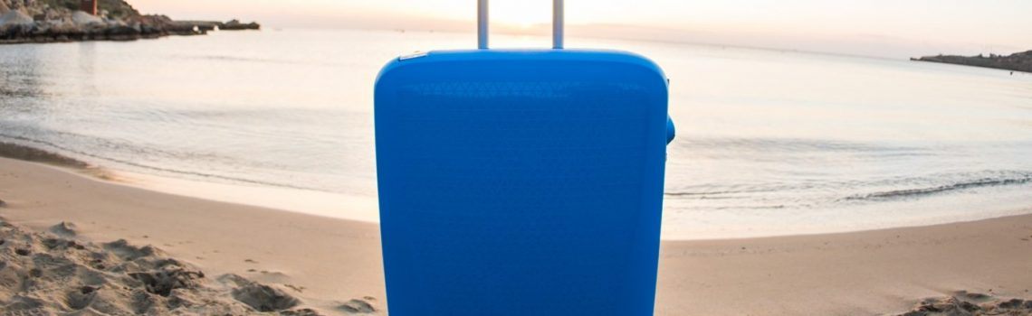 Travel, holiday and vacation concept - blue suitcase on the beach.
